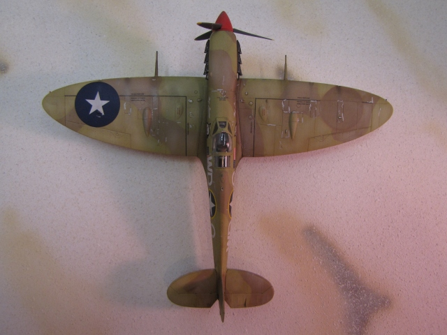 British aircraft carried roundels on both wing upper surfaces.  When the 52nd Fighter Group inherited this aircraft they painted out the starboard roundel, and modified the port one into the US insignia (ish).