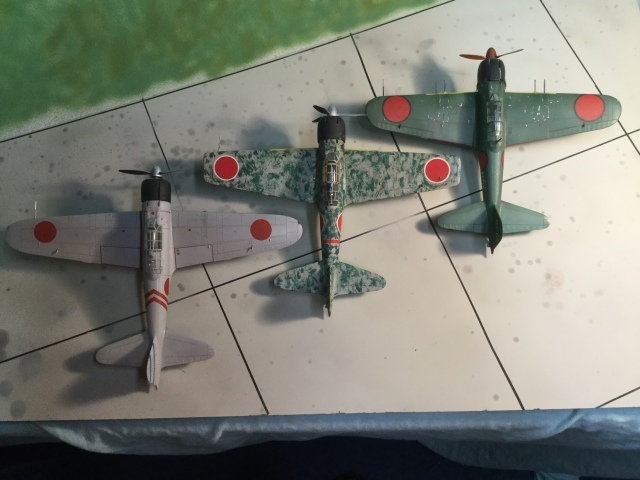 This overhead shows three major types of Zero. The A6M2 Model 21 is on the left (a model 11 was built in small numbers with the same wing shape, but no folding tips). The A6M3 Model 32 shows the new squared tips, and the enlarged engine. Also, the 20 mm cannon in the wings were an improved type with a better rate of fire. The A6M5 Model 52c right is the final major version. The wing has the same span as the Model 32 but the tips have been rounded. It also has an even more improved 20 mm cannon and a heavy machine gun in each wing. But it still uses the same engine.
